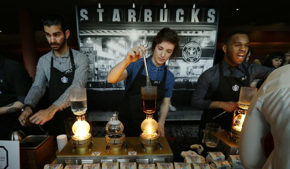 FILE - In this Wednesday, March 23, 2016, file photo, Starbucks workers prepare coffee using siphon vacuum coffee makers at a station in the lobby of the coffee company's annual shareholders meeting in Seattle. Starbucks says that it will be boosting the base pay of all employees and store managers at U.S. company-run stores by 5 percent or more on Oct. 3. In a letter sent to workers on Monday, July 11, 2016, CEO Howard Schultz said that the amount of the raise will be determined by geographic and market factors. (AP Photo/Ted S. Warren, File)